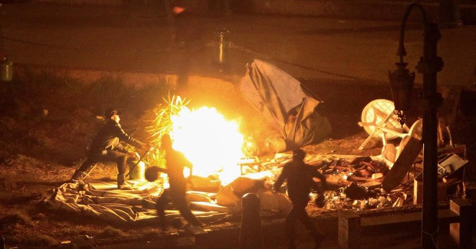 25.jan.2013 - Policial egípcio ateia fogo a barracas montadas por manifestantes na praça Tahrir, no Cairo, na madrugada de hoje, quando é comemorado o segundo aniversário da revolução que depôs o ditador Hosni Mubarak. Manifestantes se dirigem à praça para protestar contra o governo de Mohammed Mursi, aliado da Irmandade Muçulmana
