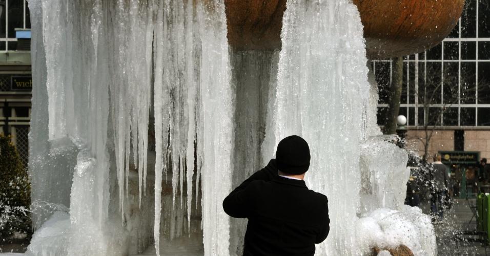 25.jan.2013- Homem fotografa fonte cuja água ficou congelada devido às baixas temperaturas, no Bryant Park, em Nova York (EUA)