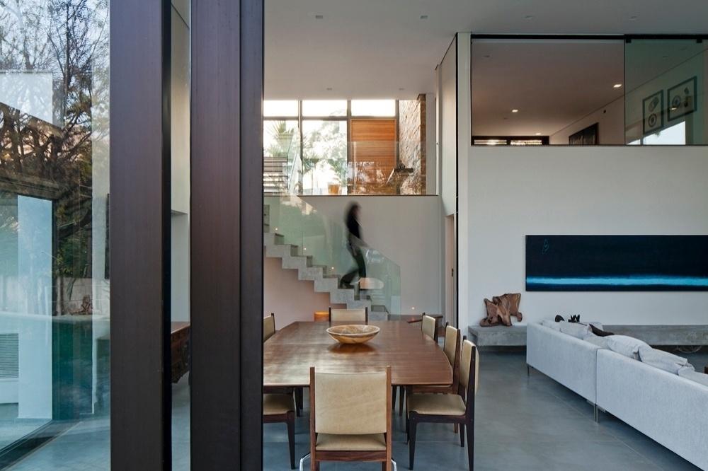 O living da casa AM (Drucker Arquitetos Associados) está um nível abaixo da entrada principal e é acessado por um novo lance de escadas, em direção aos fundos da casa. Lá em cima, separada do estar por uma grande janela de vidro de correr, com cortinas blackout tipo roll-on, está a sala de TV. A mesa de jantar é Charles Eames, com tampo em jacarandá e pés em aço inox (Móveis Teperman) e as cadeiras retas em couro bege têm design criado por Sergio Rodrigues
