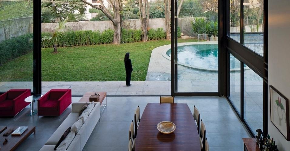 O pé direito na sala de estar não chega a ser duplo, segundo a arquiteta e projetista Monica Drucker, para que não ficasse muito alto. A entrada de luminosidade natural também pôde ser explorada a partir de grandes portas de correr de vidro que fazem o fechamento da fachada posterior, para a piscina. As mesas de canto, assim como a de jantar, possuem tampo em jacarandá e pés de aço inox; todos os sofás e as mesas de centro são Micasa