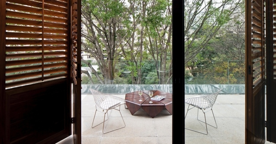 Um dos quartos de hóspedes possui varanda equipada com a mesa Pétala, em jacarandá, assinada por Jorge Zalszupin (Teperman), além de cadeiras Bertoia. O piso em granito cinza claro é jateado e antiderrapante, como na varanda do living, e o quarto tem portas-camarão venezianas em cumaru. Ao fundo, árvores preservadas, que sombreiam a casa AM no verão. A arquitetura é assinada pela arquiteta Monica Drucker