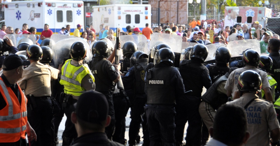 25.jan.2013 - Membros da Guarda Nacional venezuelana se abrigam durante confronto do lado de fora da penitenciária de Uribana, na cidade de Barquisimeto, noroeste da Venezuela. Ao menos 61 pessoas foram mortas e 120 ficaram feridas em confrontos entre detentos rebelados e forças policiais. Uribana é considerado o presídio mais perigoso da Venezuela
