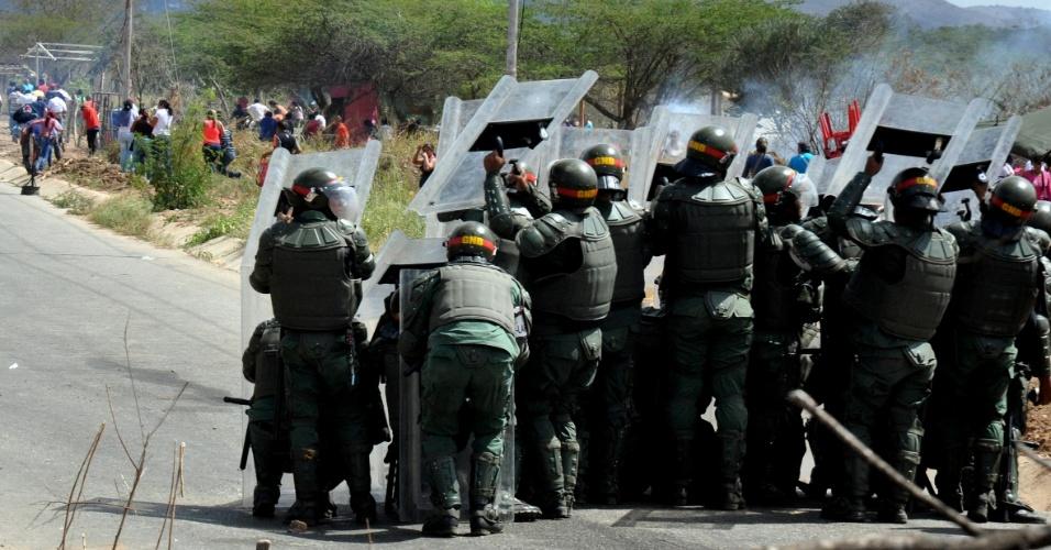25.jan.2013 - Membros da Guarda Nacional venezuelana se abrigam durante confronto do lado de fora da penitenciária de Uribana, na cidade de Barquisimeto, noroeste da Venezuela. Ao menos 61 pessoas foram mortas e 120 ficaram feridas em confrontos entre detentos rebelados e forças policiais