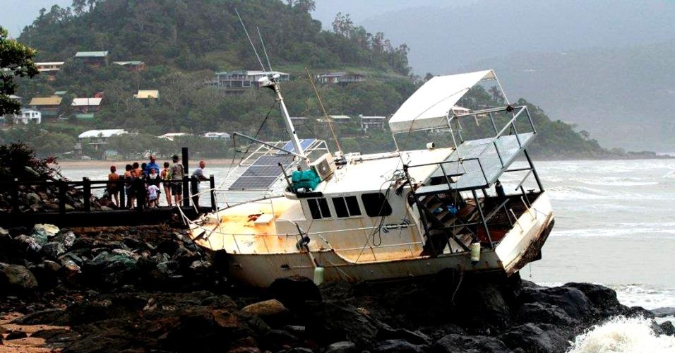 25.jan.2013 - Pessoas observam barco que foi arrastado para as pedras em praia de Arlie Beach, nordeste da Austrália, pela ressaca. Ventos e chuvas fortes, remanescentes da tempestade tropical Oswald, fecharam estradas, isolaram cidades e geraram ondas grandes no litoral australiano