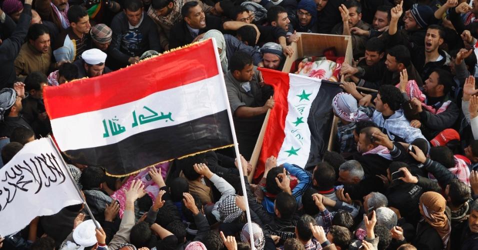 26.jan.2013 - Amigos e parentes carregam caixão de vítima morta em confrontos com forças de segurança do Iraque, em Falluja. Pelo menos três pessoas morreram durante protesto contra o primeiro-ministro  Nuri al-Maliki, na sexta-feira (25)