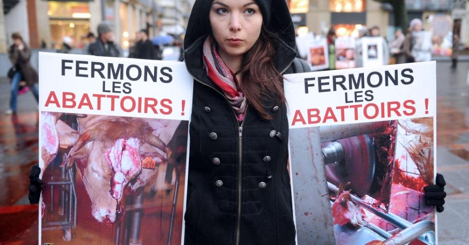 """26.jan.2013 - Mulher segura cartazes onde se lê a frase """"fechem os abatedouros"""", em protesto contra a escravidão animal, em Tolouse, na França, neste sábado (26)"""