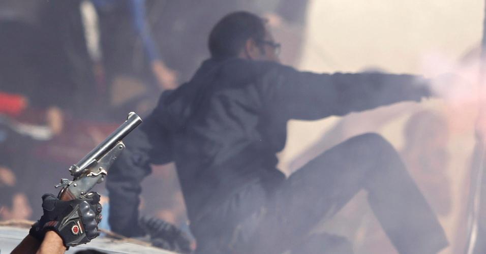 26.jan.2013 - No Cairo, torcedores do Al Ahly comemoram, com arma de brinquedo, a sentença de morte dos 21 acusados pelo massacre dos seguidores do clube no estádio de Port Said, no norte do Egito. Durante os protestos, cerca de 30 pessoas morreram