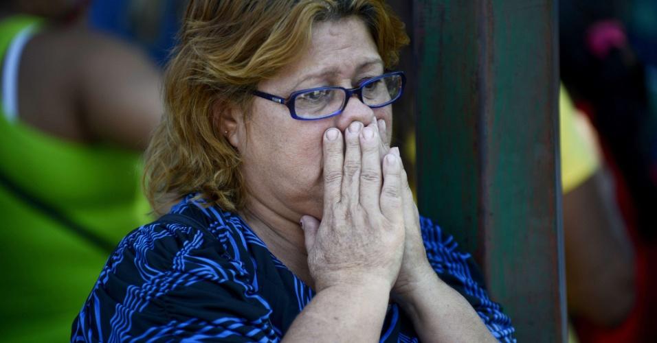 26.jan.2013 - Parente de um dos detentos mortos na sexta-feira (25) durante rebelião que eclodiu na penitenciária Uribana, no Estado de Lara, na Venezuela, espera do lado de fora de um necrotério onde o corpo será velado, neste sábado (26). O motim explodiu na sexta-feira (25), após a imprensa do país divulgar, inadvertidamente, uma operação de busca de armas dentro da penitenciária, superlotada, e considerada a mais perigosa da Venezuela. Pelo menos 54 pessoas foram mortas e 90 ficaram feridas