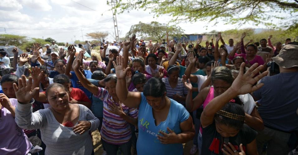 26.jan.2013 - Parentes de presidiários rezam fora da penitenciária Uribana, no Estado de Lara, na Venezuela, neste sábado (26), um dia após o motim que deixou pelo menos 61 mortos e 120 feridos