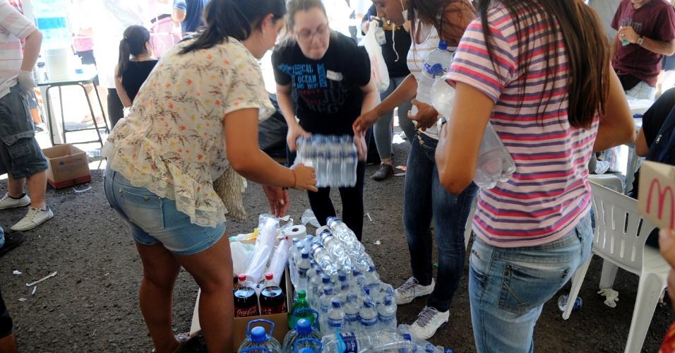27.jan.2013 - Voluntários organizam água e outros mantimentos no Centro Desportivo Municipal de Santa Maria, que serão oferecidos a parentes e amigos durante o velório coletivo