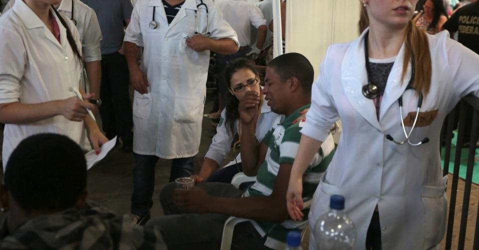 27.jan.2013 - Enfermeiros atendem familiares que passaram mal enquanto participavam de velório coletivo das vítimas do incêndio que atingiu uma boate de Santa Maria (RS) na madrugada deste domingo (27), em um dos ginásios do Centro Desportivo Municipal