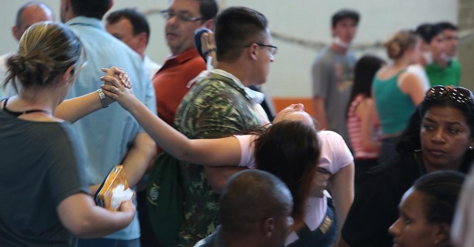 27.jan.2013 - Familiares passam mal enquanto participam de velório coletivo das vítimas do incêndio que atingiu uma boate de Santa Maria (RS) na madrugada deste domingo (27), em um dos ginásios do Centro Desportivo Municipal