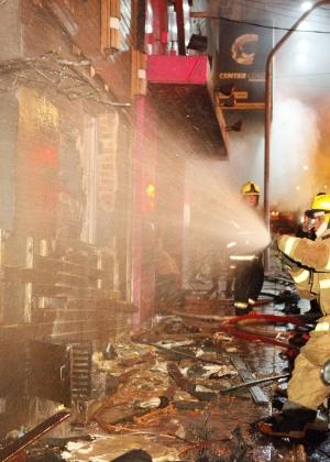 Bombeiros trabalham no incêndio, na madrugada de domingo (27)
