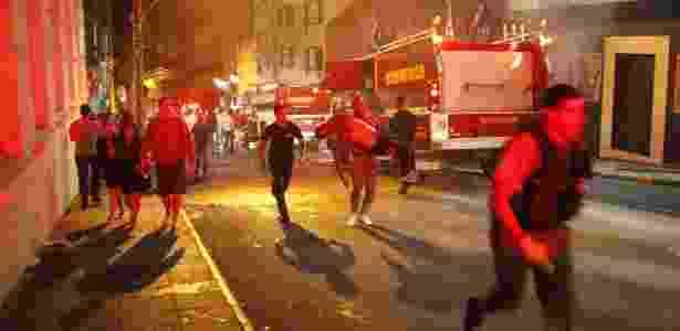 Ezequiel Corte Real (ao centro) carrega corpo de vítima no incêndio da boate Kiss, no domingo (27) - Germano Roratto/Agência RBS