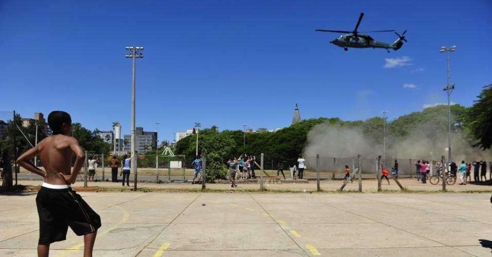 27.jan.2013 - Pessoas observam helicóptero que chega a Porto Alegre, vindo de Santa Maria (RS), trazendo vítimas do incêndio na boate Kiss para serem encaminhadas à hospitais da cidade. Mais de 200 pessoas morreram na tragédia