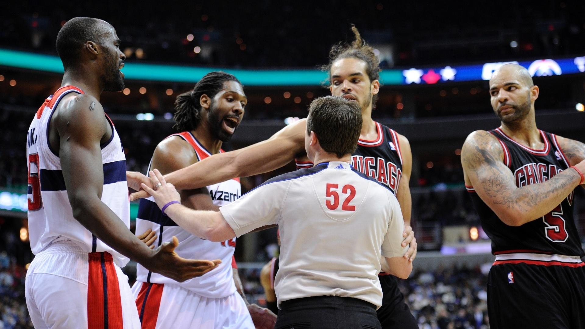 Árbitro interveem na discussão entre Emeka Okafor (e), o brasileiro Nenê, dos Wizards, e Joakim Noah e Carlos Boozer (d), do Chicago Bulls