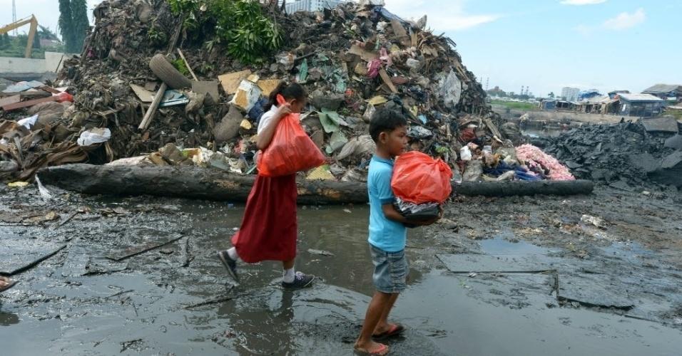 28.jan.2013 - Criança carregam mantimentos doados por entidade em Jacarta (Indonésia). Ao menos 32 pessoas morreram  nas  inundações  por causa de fortes tempestades no país