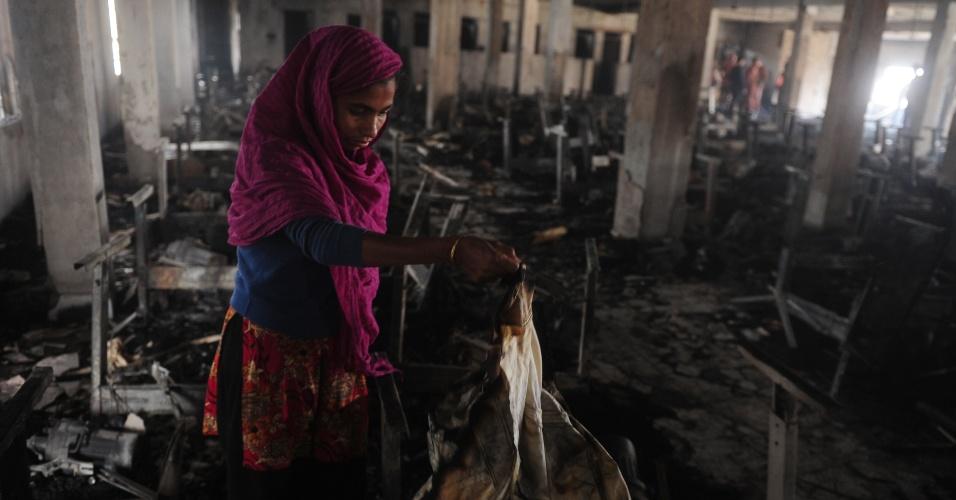 28.jan.2013 - Operária observa destroços deixados pelo incêndio que devastou uma fábrica de roupas em Dacca, Bangladesh, no sábado (27). Pelo menos sete mulheres trabalhadoras foram mortas
