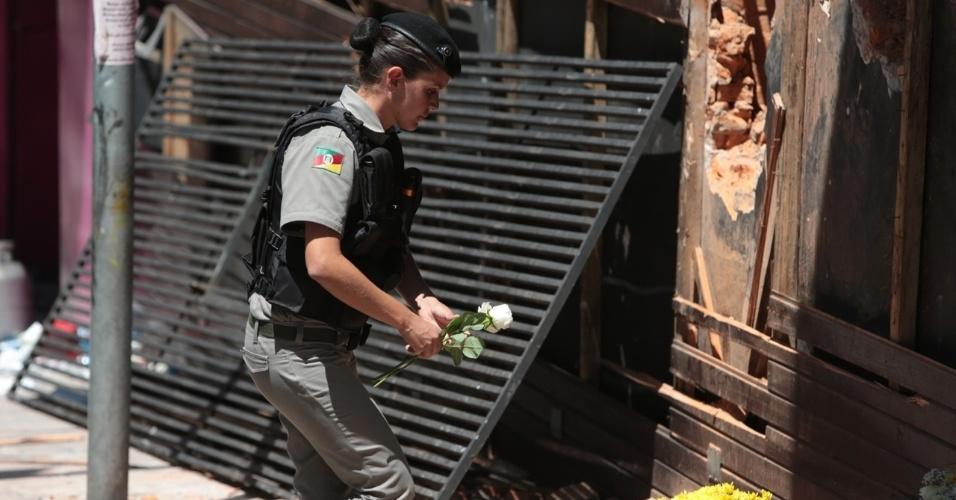 28.jan.2013 -  Policial deixa flores na entrada da boate Kiss em homenagem às vítimas do incêndio que deixou mais 230 pessoas mortas. A polícia do Rio Grande do Sul já ouviu cerca de 20 testemunhas do incêndio e  pretende se concentrar nos esforços de investigação da tragédia