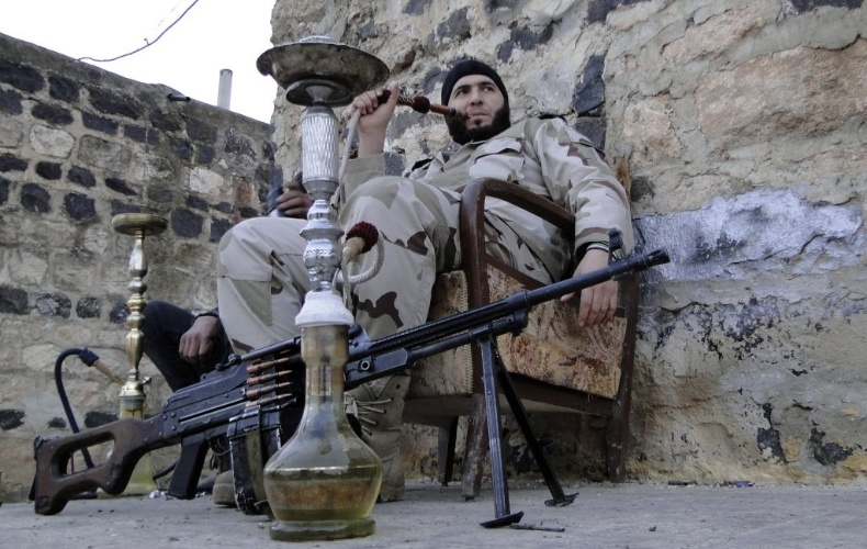 28.jan.2013 - Rebelde sírio fuma cachimbo d'água próximo ao aeroporto militar de Menagh, no interior de Aleppo