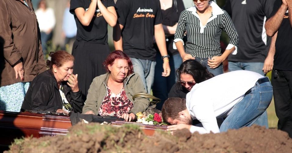 28.jan.2013- Homem beija o caixão com o corpo de Tanise Lopes Cielo, uma das vítimas do incêndio em uma boate em Santa Maria (RS), no cemitério municipal da cidade