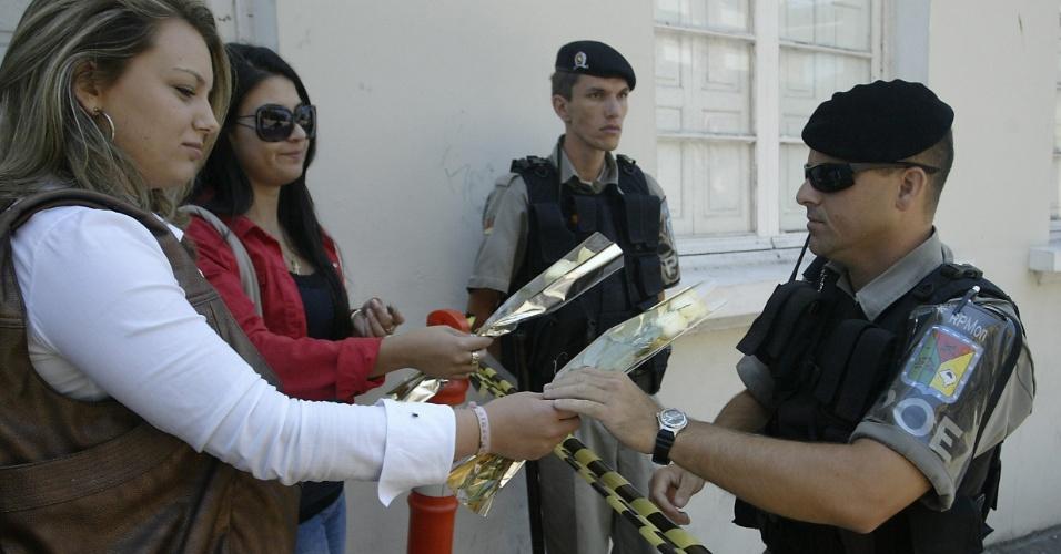 28.jan.2013- Mulheres entregam flores a um soldado para que sejam colocadas em frente à boate Kiss, em Santa Maria (RS), onde um incêndio na madrugada de domingo deixou mais de 230 mortos