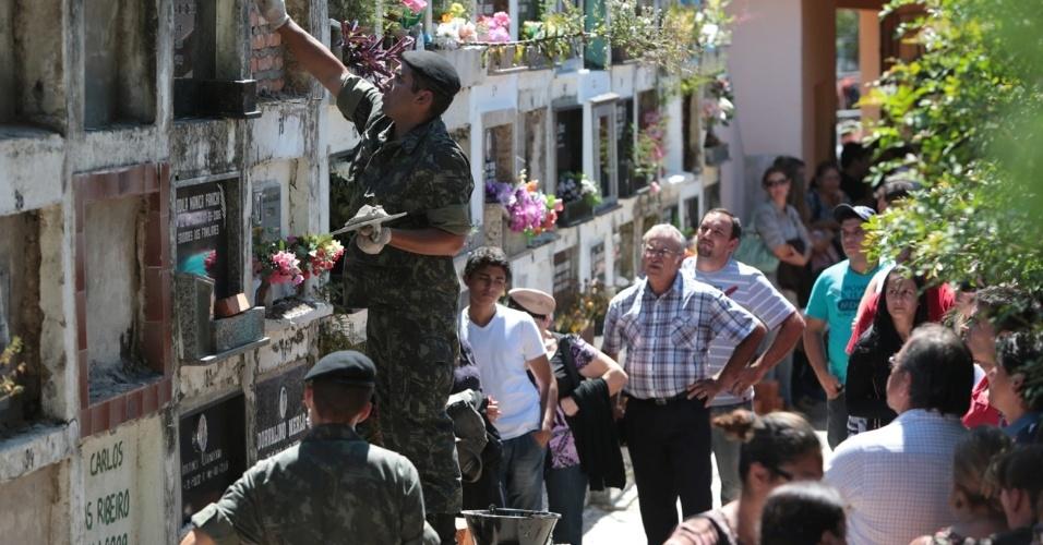 28.jan.2013- Soldado do Exército ajuda no enterro de vítimas do incêndio em uma boate em Santa Maria (RS), no cemitério municipal da cidade