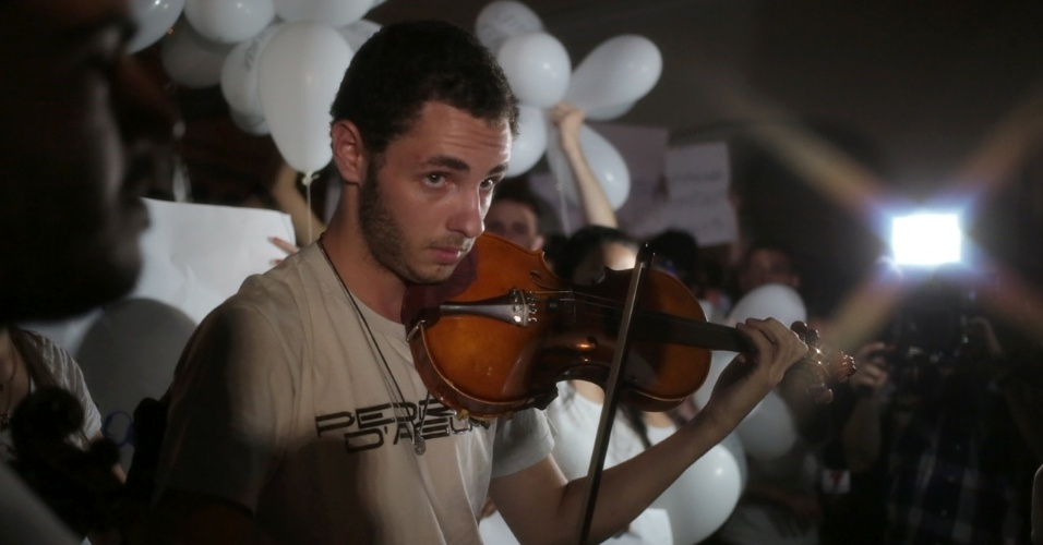 28.jan.2013 - Manifestantes tocam violino durante passeata pela paz, realizada na praça Saldanha Marinho, em Santa Maria (RS), em homenagem às vítimas do incêndio na boate Kiss, que matou 231 pessoas