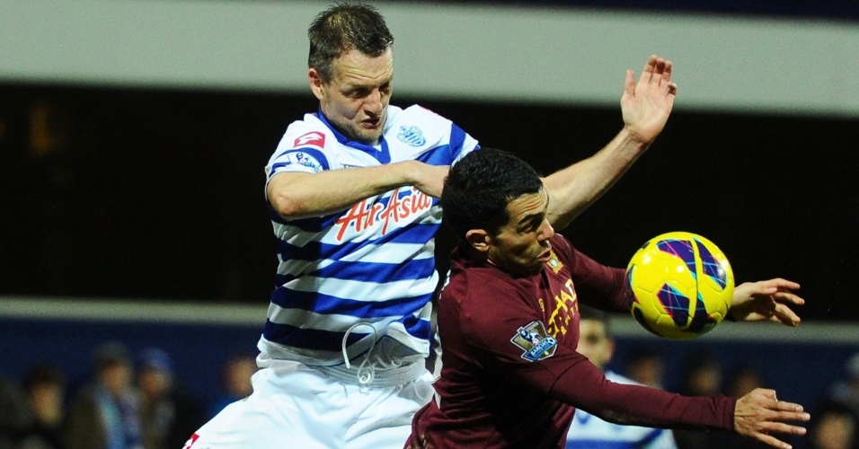 29.jan.2013 - Carlitos Tevez (dir), do Manchester City, disputa bola no alto com Clint Hill, do QPR, durante jogo do Campeonato Inglês