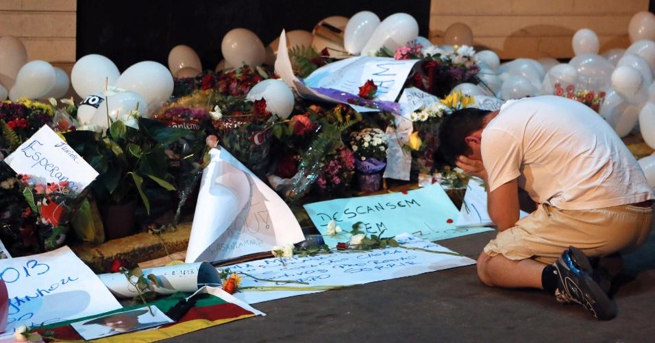 29.jan.2013- Garoto se ajoelha e chora ao lado das flores e cartazes deixados na porta da boate Kiss, em Santa Maria (RS), onde um incêndio na madrugada de domingo (27) procovou a morte de mais de 200 pessoas