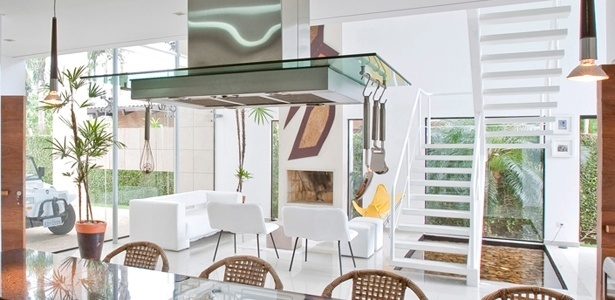 No projeto de Flavio Castro, paredes inteiramente envidraçadas banham sala e cozinha integradas de luz - Divulgação