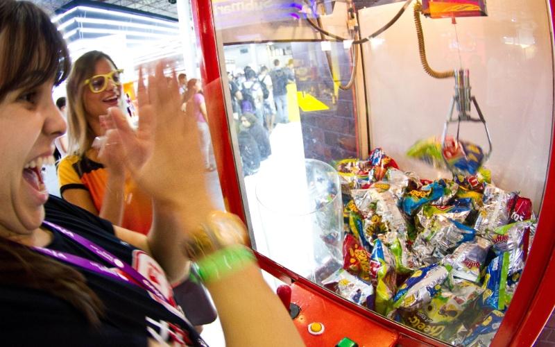 29.jan.2013 - No espaço do UOL, na área Expo (acessível inclusive para quem não está acampado), os visitantes podem brincar nesta máquina, onde devem tentar pegar salgadinhos: é a Nerdelicious