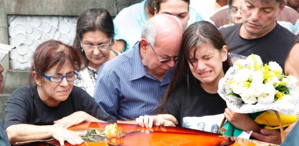 Ao lado dos avós, a filha da capitã do Exército Daniele Dias de Mattos se emociona durante o sepultamento da militar no Cemitério de Inhaúma, zona norte do Rio de Janeiro - Marco Antônio Teixeira/UOL