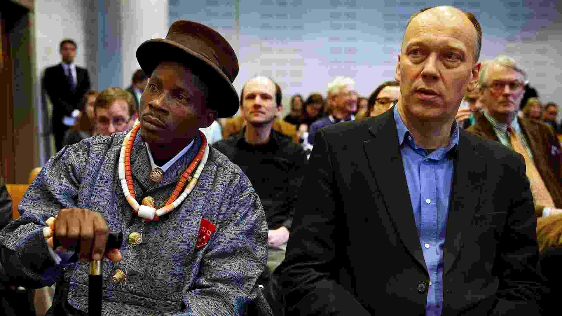30.jan.2013 - O fazendeiro nigeriano Eric Dooh, que abriu ação contra a Shell Nigeria, senta ao lado de Geert Ritsema, líder da ONG ecológica Milieudefensie, em uma corte da Holanda, nesta quarta-feira. A filial da petroleira foi condenada pela Justiça holandesa por poluir o delta do rio Níger, no sul do país, e terá de pagar indenização ao agricultor - Jerry Lampen/AFP