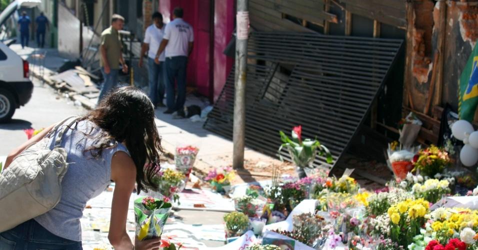 30.jan.2013 - Parentes e amigos das vítimas do incêndio na boate Kiss, em Santa  Maria (RS), deixam flores no local da tragédia, que foi transformado numa espécie de memorial. Mais de 230 pessoas morreram no incêndio