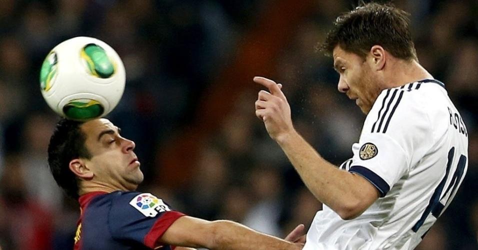 30.jan.2013 - Xavi (esq.), do Barcelona, disputa a bola com Xabi Alonso, do Real Madrid, em partida da Copa do Rei da Espanha