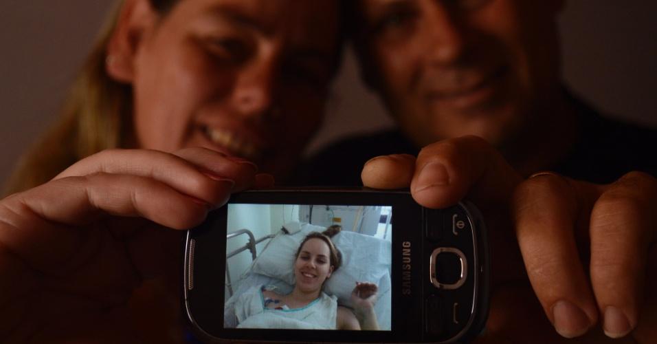 31.jan.2013 - Eliete e Flávio, pais de Ingrid Preigschadt Goldani, 21, mostram foto da filha internada em um hospital de Porto Alegre (RS). Ela foi uma das sobreviventes do incêndio na boate Kiss, em Santa Maria (RS), e na falta da fala ainda tímida, por conta do tubo instalado em sua traqueia durante dois dias para permitir a respiração, a estudante de enfermagem recorre à mímica para tranquilizar os pais. Deitada em um leito na UTI do Hospital Conceição, em Porto Alegre(RS), junta as mãos para formar um coração, apontado afetuosamente para o casal