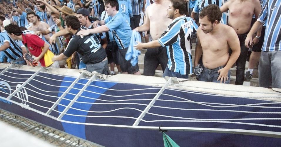 31.jan.2013 - Torcida do Grêmio olha o alambrado caído após Avalanche da torcida