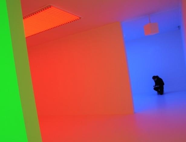 """A exposição """"Light Show"""" (""""Show de luz"""", em tradução livre), na Hayward Gallery, em Londres, reúne instalações e esculturas de artistas que manipulam e experimentam com a natureza da luz artificial. Acima, uma mulher vê o trabalho """"Cromosaturação"""", do artista venezuelano Carlos Cruz-Diez - Emma Lynch/BBC"""