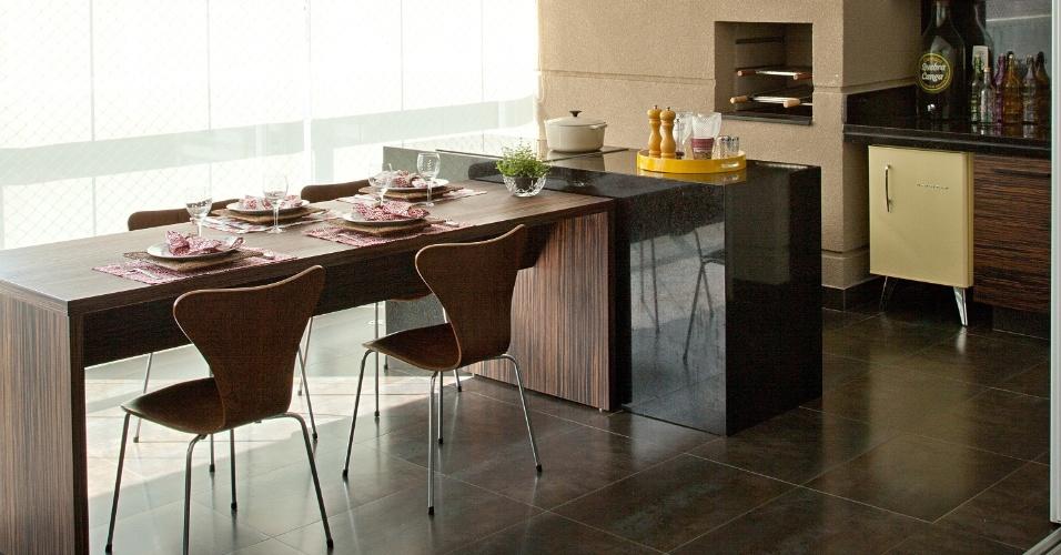 A varanda gourmet projetada pela arquiteta Patricia Pasquini conta com churrasqueira e uma ilha em granito com cooktop. As cadeiras Anne Jacobsen, peças antigas do proprietário, foram restauradas