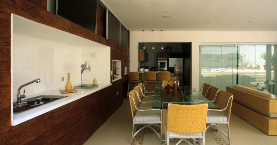 Assinada pela arquiteta Cristiane Schiavoni, a ampla varanda gourmet conta com churrasqueira, uma extensa bancada com pia e chopeira, e ao fundo, uma cozinha de apoio. O painel de madeira à direita proporciona unidade ao ambiente