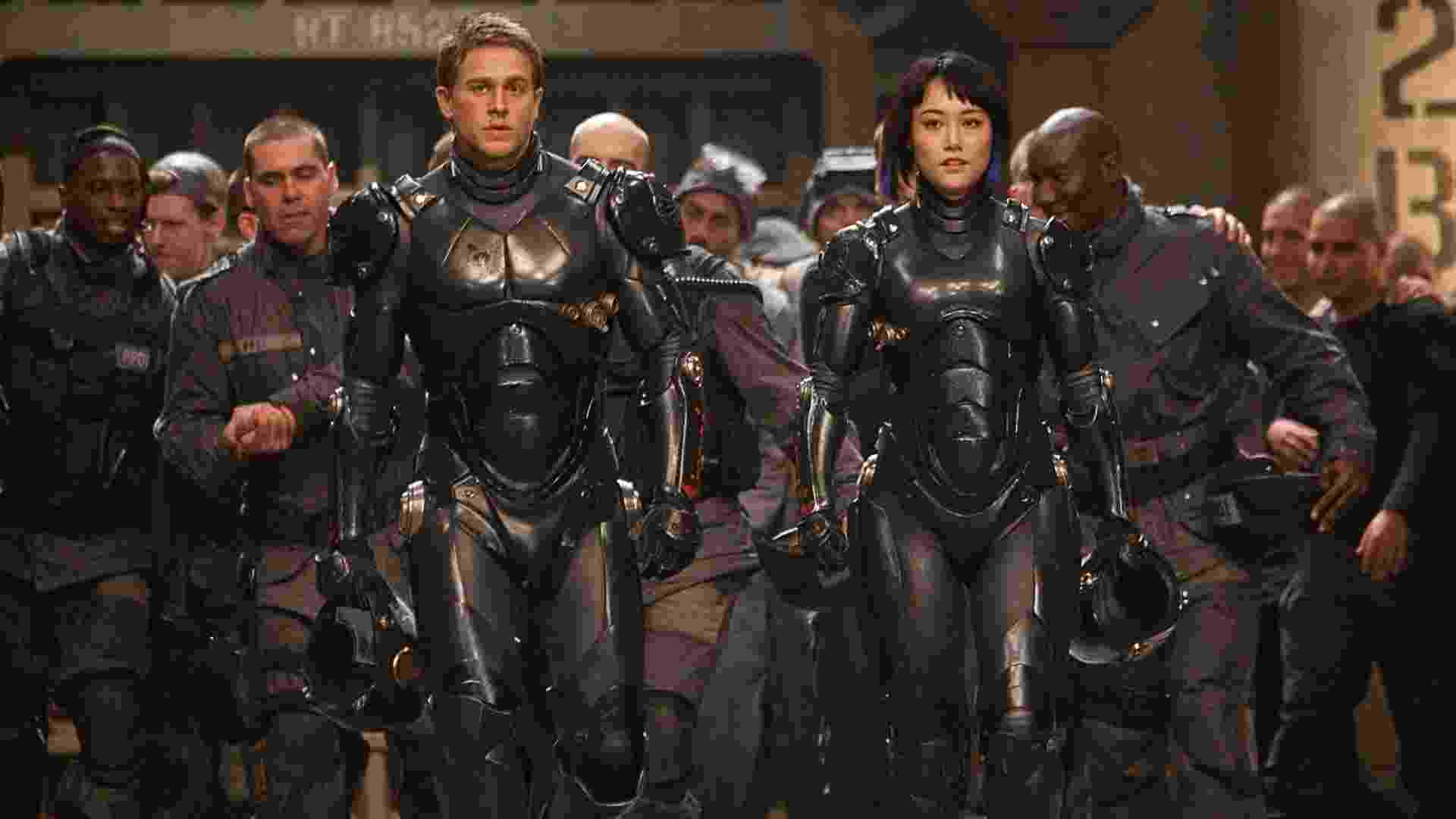 """Charlie Hunnam é um ex-piloto que se une à novata interpretada por Rinko Kikuchi para formar uma equipe que pilotará um robô Jaeger para defender a humanidade contra as criaturas chamadas Kaiju; no novo longa de Guillermo del Toro, """"Círculo de Fogo"""" - Divulgação"""