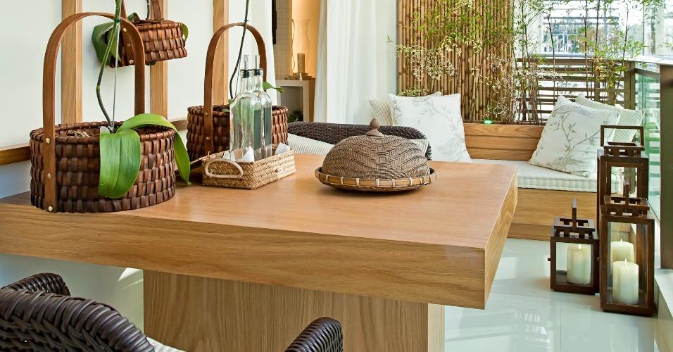 Como a dimensão da varanda gourmet era pequena, a arquiteta Maithiá Guedes optou por uma mesa de apenas dois lugares. Além de um espaço para as refeições, o sofá do tipo futon (ao fundo) e a decoração zen são propícias aos momentos de relaxamento