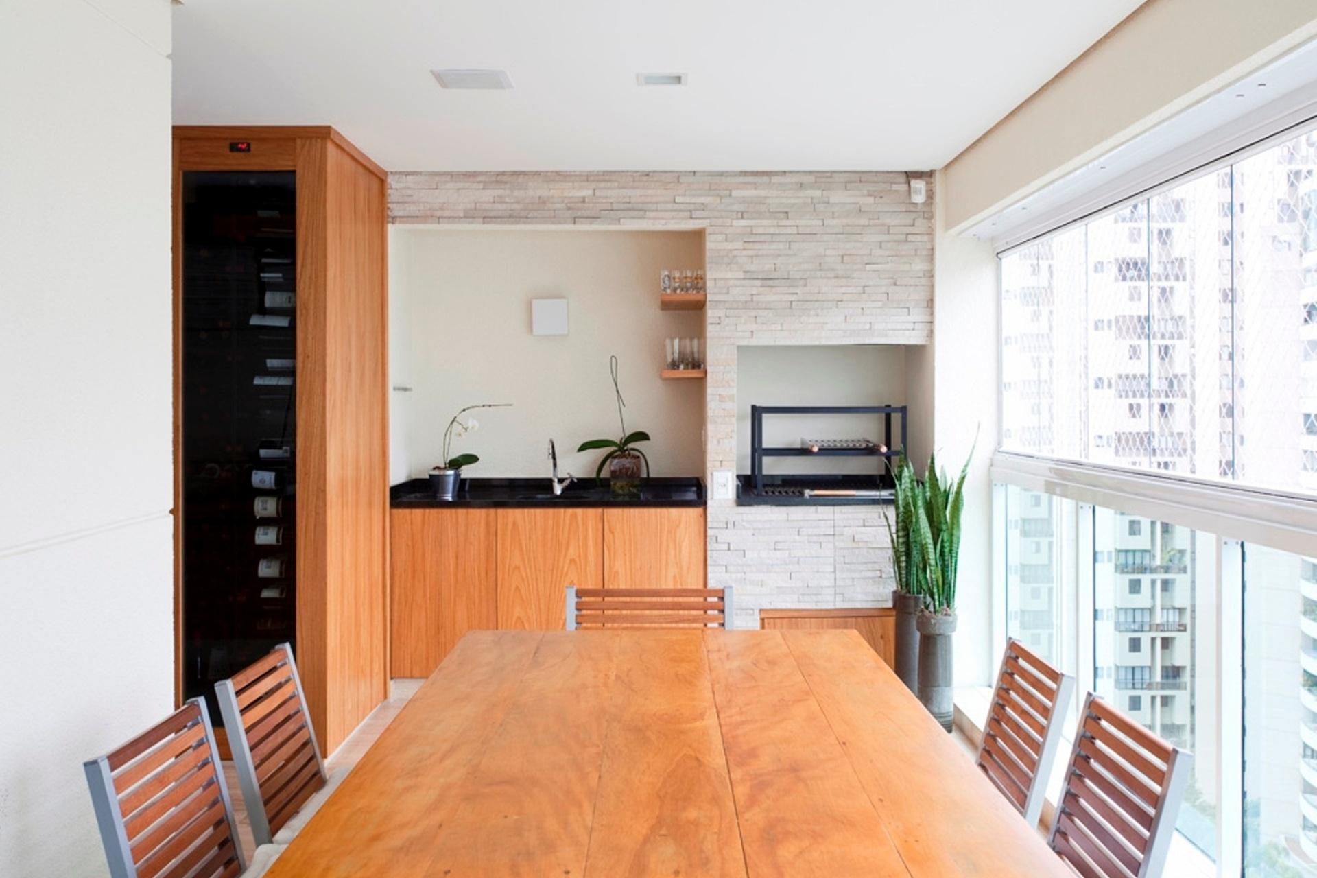 No apartamento projetado pelo escritório FGMF Arquitetos, em São Paulo (SP), além da churrasqueira e da bancada, equipa a varanda gourmet com uma adega, feita sob medida para o cliente
