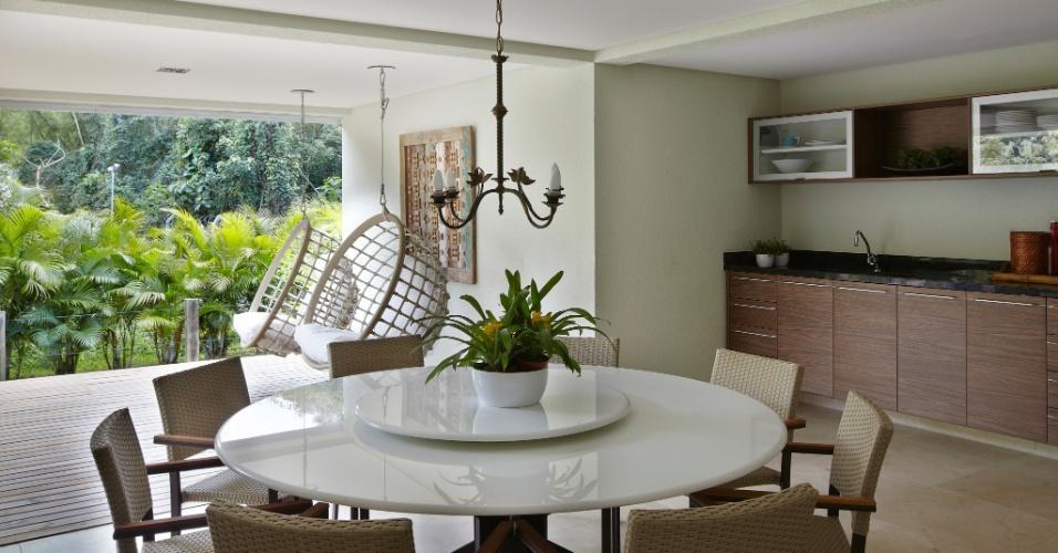 No projeto desta charmosa varanda gourmet, as arquitetas Giselle Macedo e Patrícia Covolo priorizaram a circulação dos moradores e amigos ao dispor a mesa redonda no centro do ambiente e a bancada junto à parede