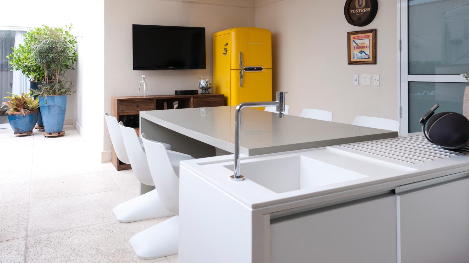 Para aproveitar melhor o espaço disponível, os arquitetos Olegário Sá e Gilberto Cioni escolheram para varanda gourmet uma mesa retangular junto à bancada. Destaque para a geladeira na cor amarela e desenho
