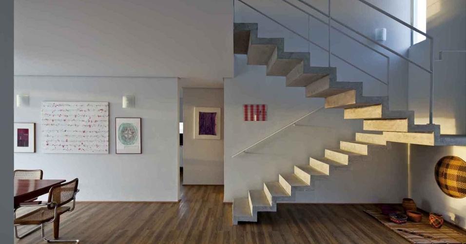 A escada em dois lances foi executada em concreto e tem corrimão metálico. À esquerda, o vão dá acesso ao lavabo e à cozinha da Casa do Moinho, projetada pela arquiteta Nora de Queiroz