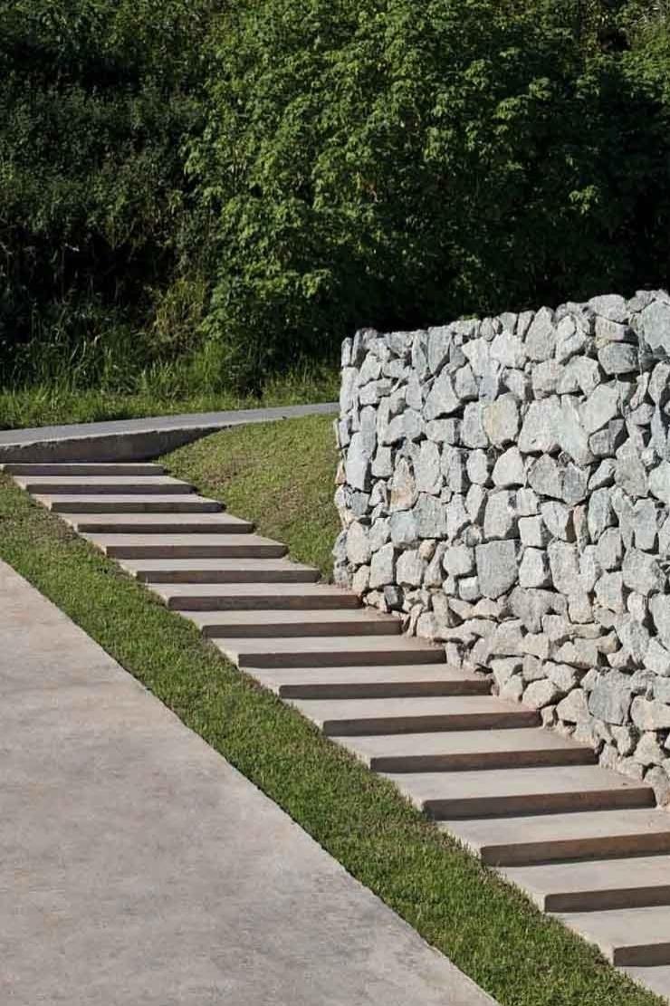 O desnível entre a rua e o pavimento térreo da residência é vencido por uma escada ladeada pela vegetação e pelo muro de pedras. A Casa do Moinho tem projeto da arquiteta Nora Queiroz