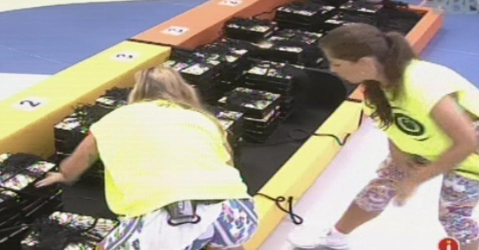 03.fev.2013 - Mariejn e Andressa tentam desembrulhar as peças do quebra-cabeça na prova da comida
