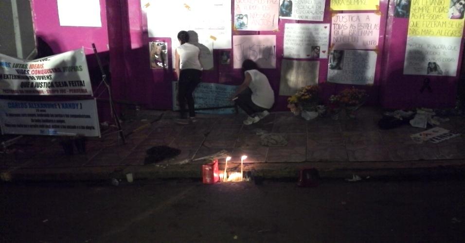 3.fev.2013 - Participantes da vigília em frente à boate Kiss, em Santa Maria (RS), neste sábado (2), fixam cartazes na parede, com mensagens de homenagem, protesto e pedidos de justiça. Centenas se reúnem para lembrar os 237 mortos no incêndio do último domingo (27)